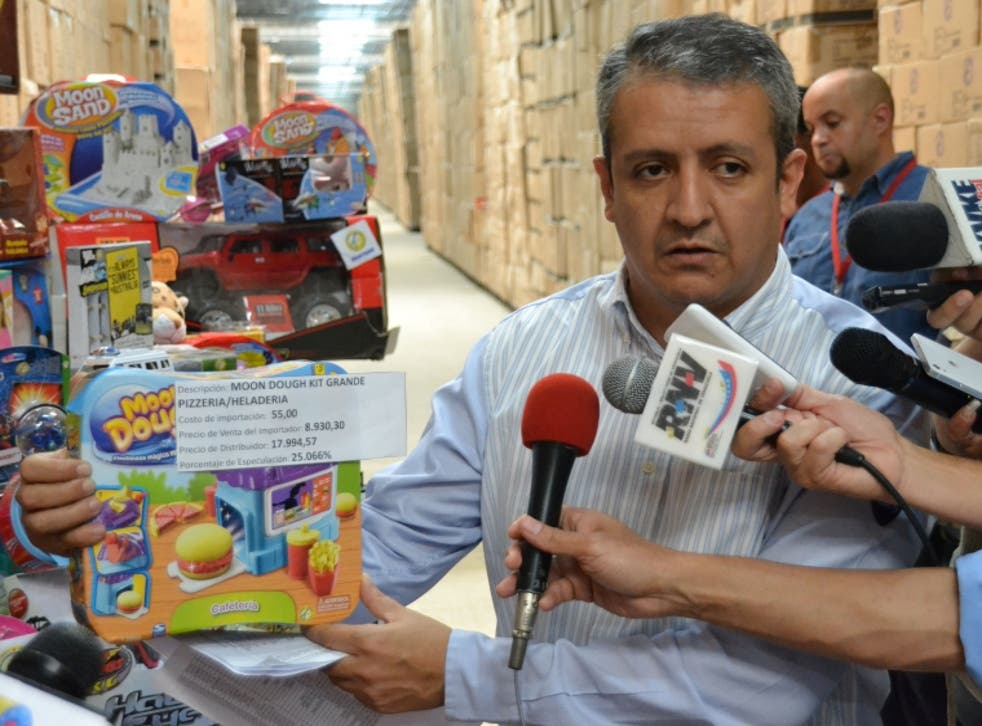 William Contreras, the head of the Venezualan agency charged with battling price-fixing, poses with some of the 4 million impounded toys