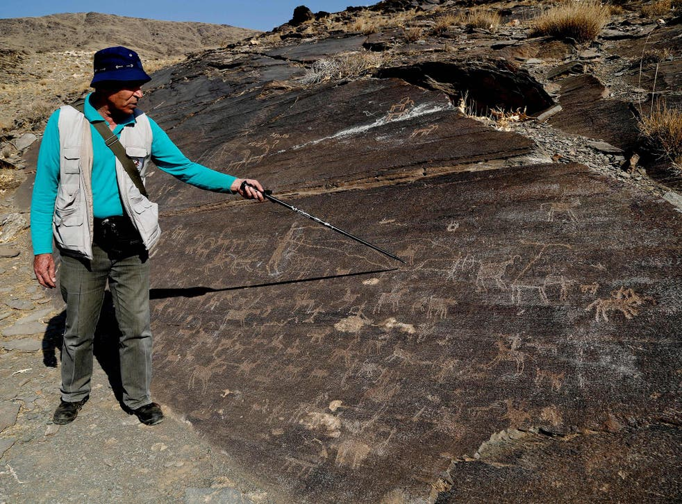 Iranian archeologist Mohammed Naserifard displays ancient engravings in the hills outside the town of Khomeyn