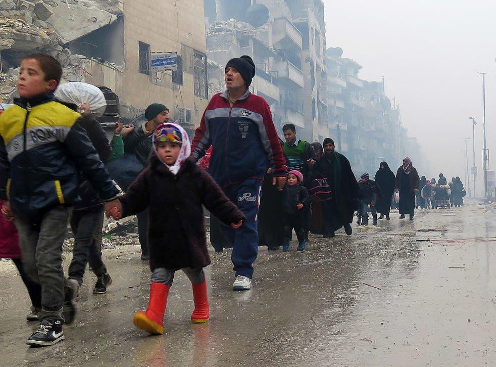 Syrian residents, fleeing violence in the restive Bustan al-Qasr neighbourhood, arrive in Aleppo's Fardos neighbourhood, after regime troops retook the area from rebel fighters