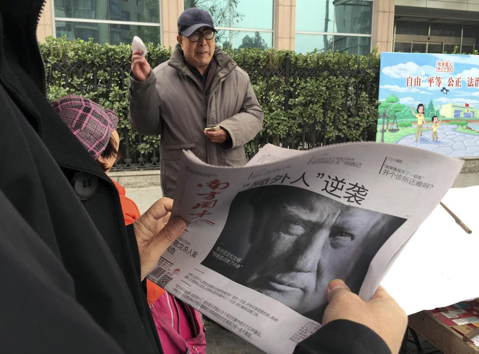 A Chinese man holds up a Chinese newspaper with the front page photo of US President-elect Donald Trump
