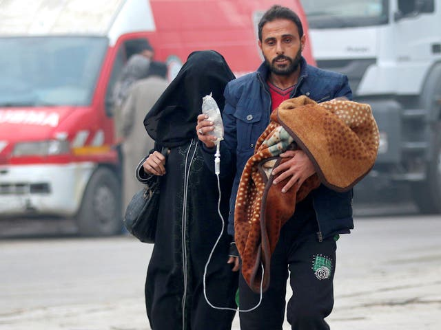 A man carries a child with an IV drip as he flees deeper into the remaining rebel-held areas of Aleppo, Syria