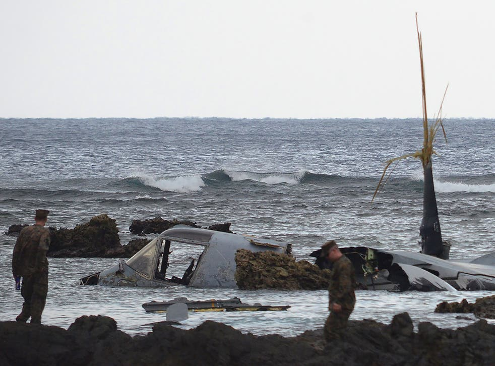 The wreckage of a US Marine MV-22 Osprey tilt-rotor aircraft is seen as the tide recedes on the coast of Nago, Japan's southern island of Okinawa, after it crash landed in shallow waters