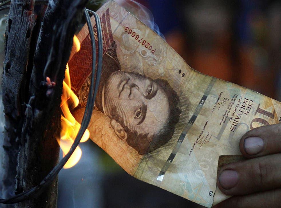 A man burns a 100-bolivar bill during a protest in El Pinal