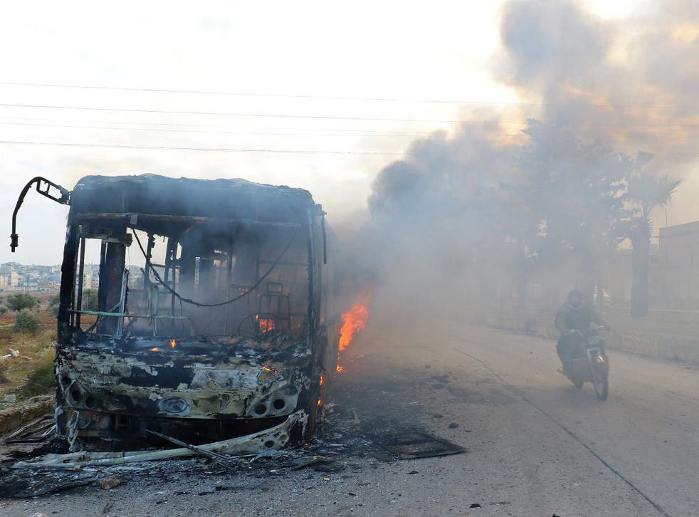 A man on a motorcycle drives past burning buses while en route to evacuate ill and injured people from the besieged Syrian villages of al-Foua and Kefraya, after they were attacked and burned, in Idlib province, Syria