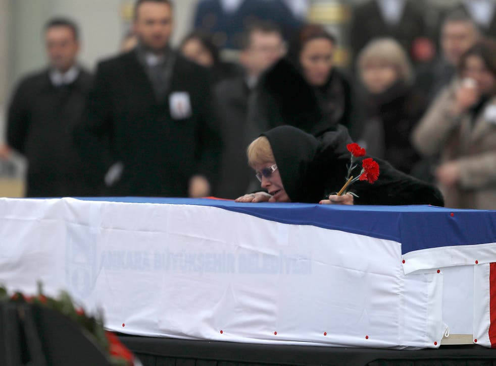 Late Russian Ambassador to Turkey Andrei Karlov's wife Marina mourns next to the flag-wrapped coffin during a ceremony at Esenboga airport in Ankara, Turkey