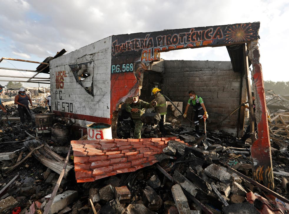 Firefighters and rescue workers remove debris from the scorched ground of Mexico's fireworks market in Tultepec