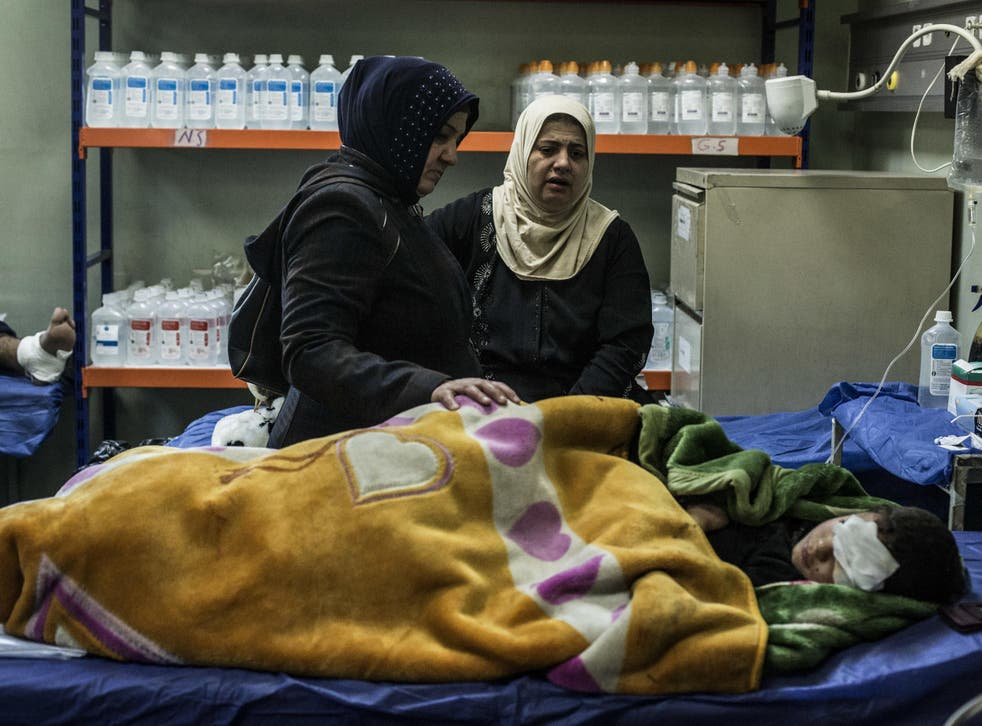 The mother and aunt of a boy wounded in a car bomb attack in the district of Gogjali in Mosul comfort him in a hospital in Irbil, Iraq