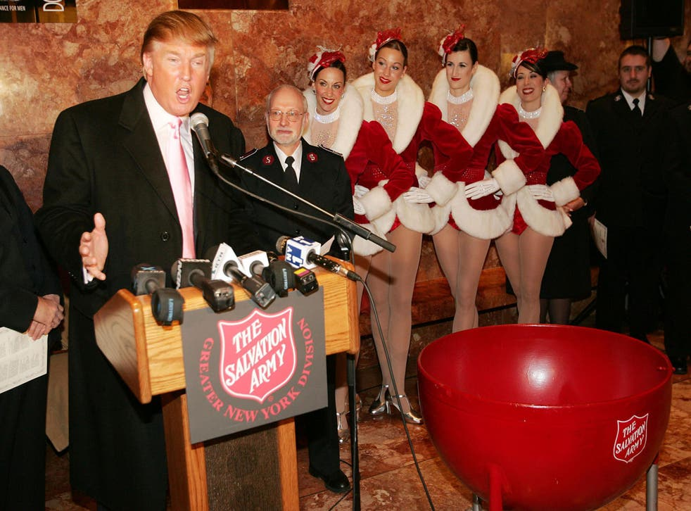 Members of the Radio City Rockettes listen to Donald Trump speaking at a Christmas ceremony in Trump Tower, New York 2004