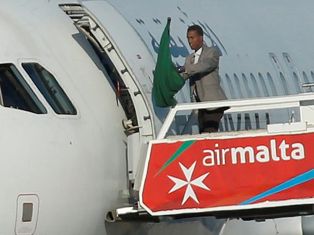 One of the hijackers of a Libyan Afriqiyah Airways Airbus A320 waves a Gaddafi-era Libyan flag at Malta Airport