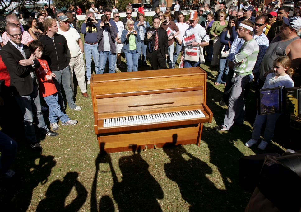 People gather around the piano which John Lennon used to compose the song 'Imagine'