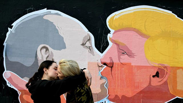 A lesbian couple kisses in front of mural depicting Russian President Vladimir Putin and Republican presidential candidate Donald Trump, on the walls of a barbecue bar 'Keule Ruke' on May 19, 2016 in Vilnius, Lithuania.