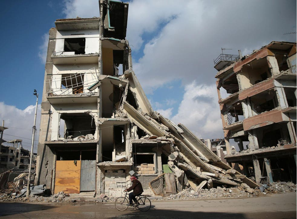 A man rides a bicycle near damaged buildings in the rebel held besieged city of Douma, in the eastern Damascus suburb of Ghouta, Syria, 30 December, 2016