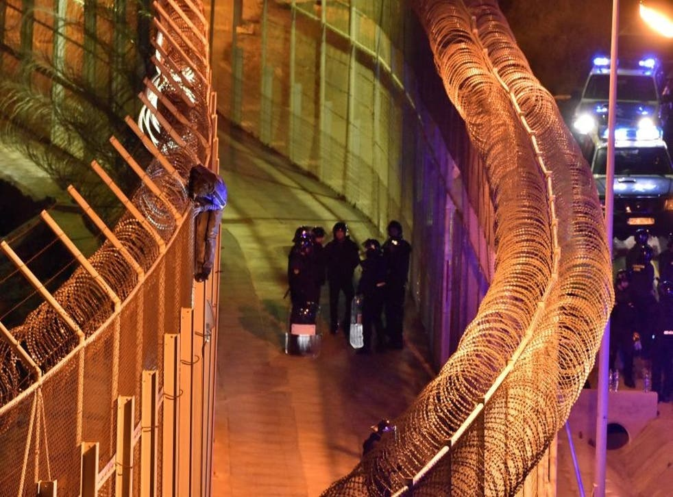 Spanish border guards look on as a migrant attempts to climb the fences in ceuta