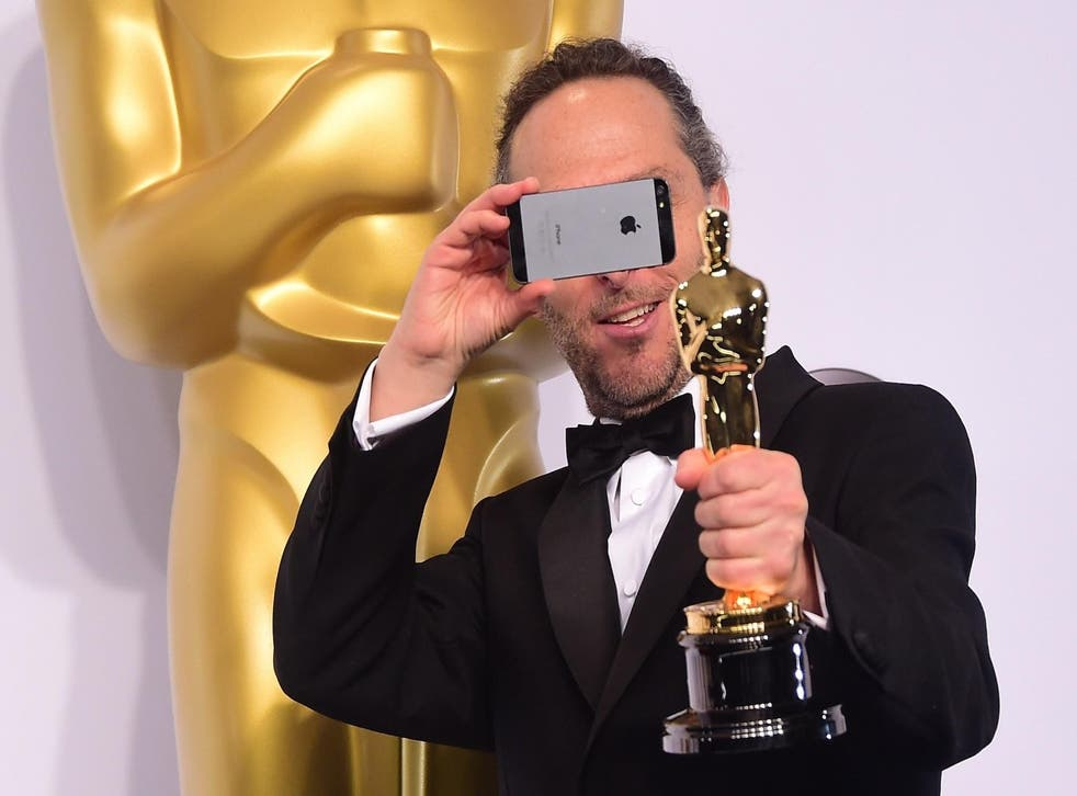 Emmanuel Lubezki, winner for the Best Cinematography Award for 'Birdman' takes a photo in the press room during the 87th Oscars on February 22, 2015 in Hollywood, California