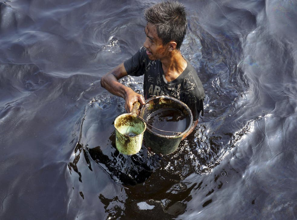 A fisherman collects spilled crude oil at the Pantai Teluk Penyu in Cilacap, Indonesia