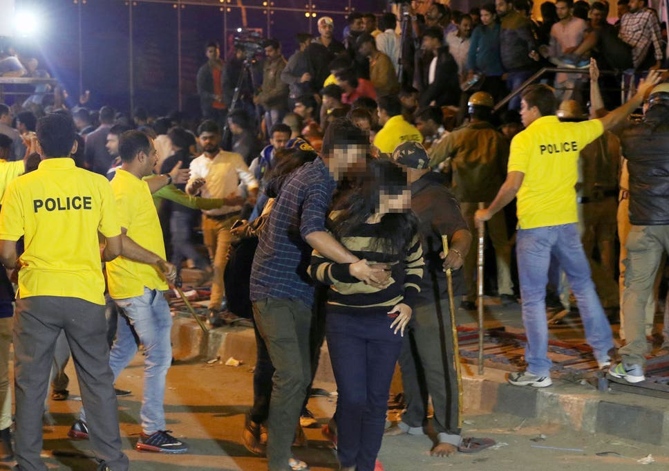 A man helps a woman leave as police try to manage crowds during New Year's  Eve