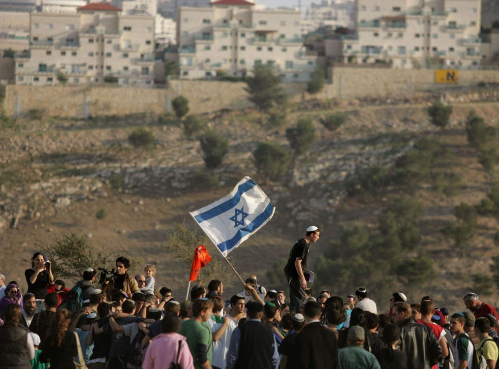 Israeli settlers dance and sing near the Israeli settlement of Maale Adumim in the West Bank