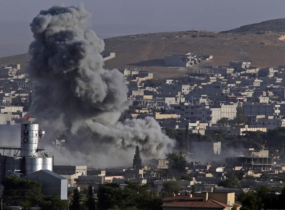 Smoke rises following an air strike by the US-led coalition in Kobani, Syria, during fighting between Kurds and Isis in October 2014