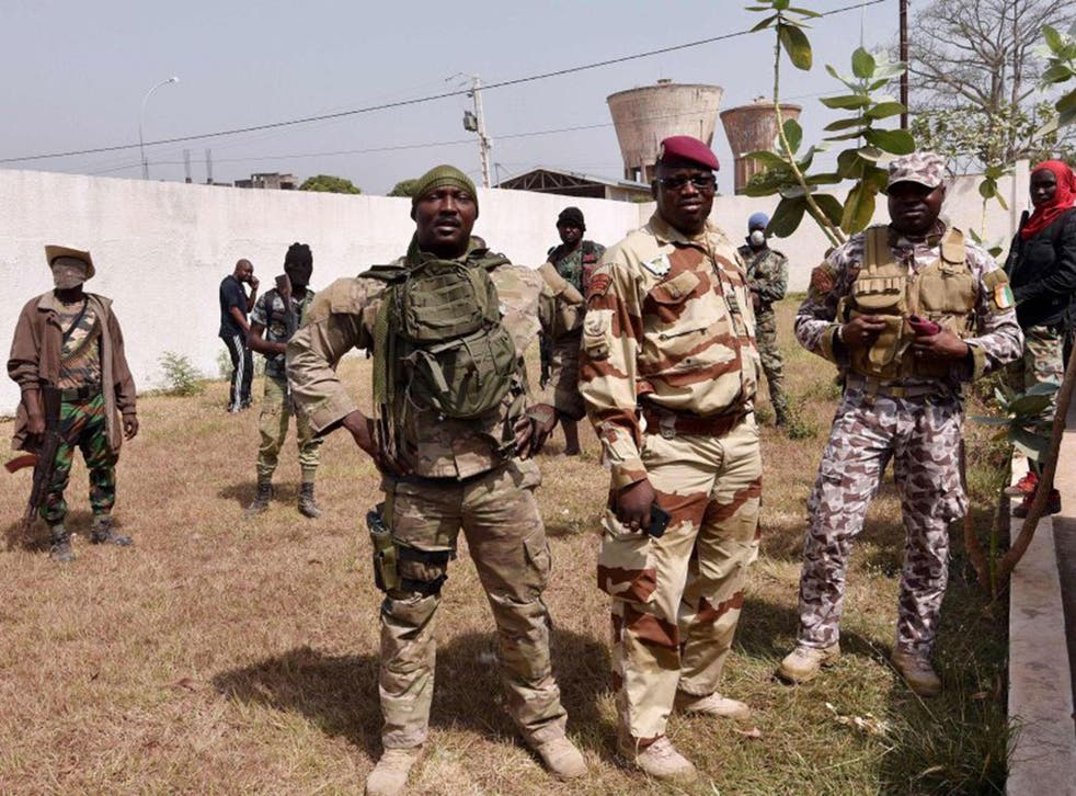 Lieutenant-colonel Issiaka Ouattara (centre), also known as Wattao, flanked by soldiers, arrives at the deputy prefect's residence in Bouake for talks with the deputy prefect and Defence Minister Alain-Richard Donwahi