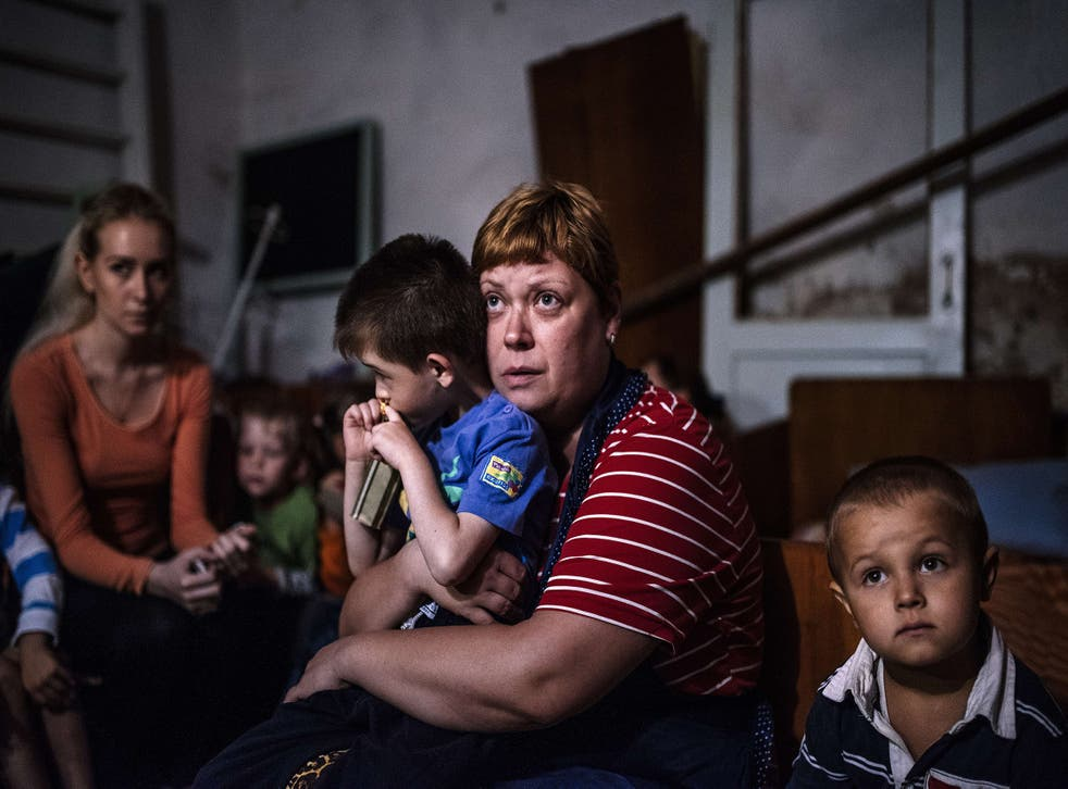 Children and teachers hide in a bomb shelter in an orphanage during a shelling in the town of Makiyivka in 2014