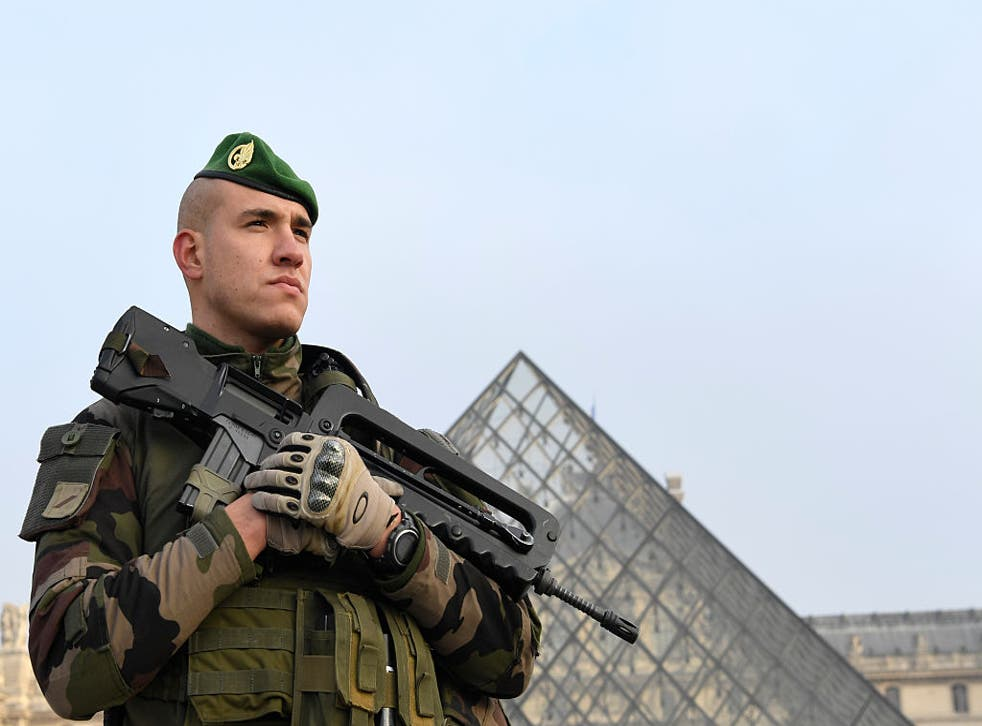 A soldier stands guard at the entrance of the Louvre museum in Paris