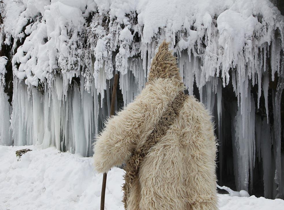 A man passes by a frozen waterfall at around minus 26 degrees Celsius (minus 14.8 degrees Fahrenheit) in the village of Jezerc, Kosovo