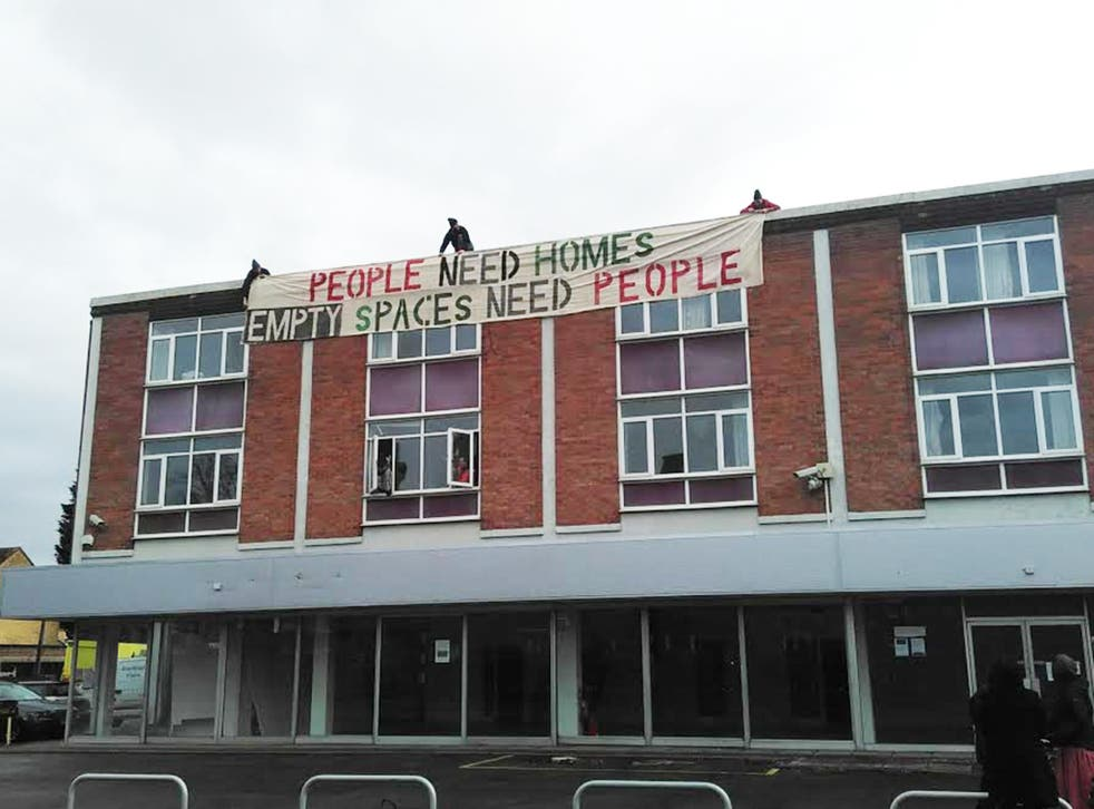 Activists drop a banner from the Iffley Road building, owned by Wadham college