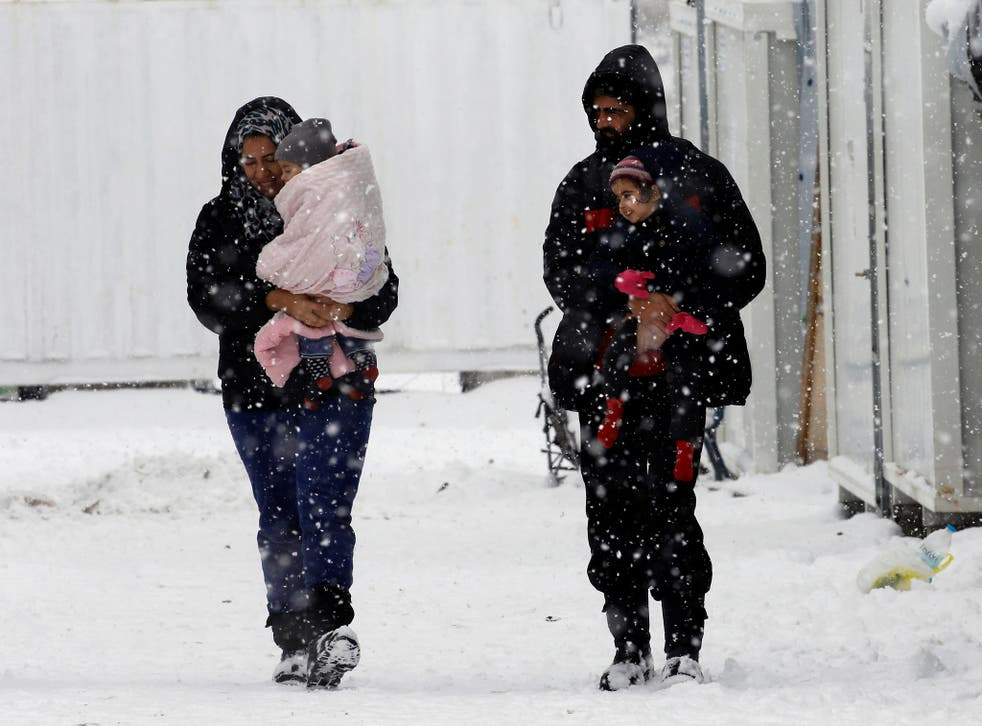 Syrian refugees carry their children through a snow storm at a refugee camp north of Athens, Greece, on 10 January