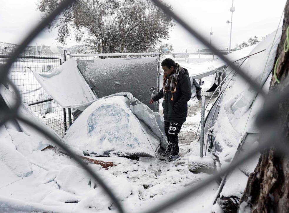 A migrant stands next to a snow-covered tent at the Moria detention camp on the Greek island of Lesbos on 7 January