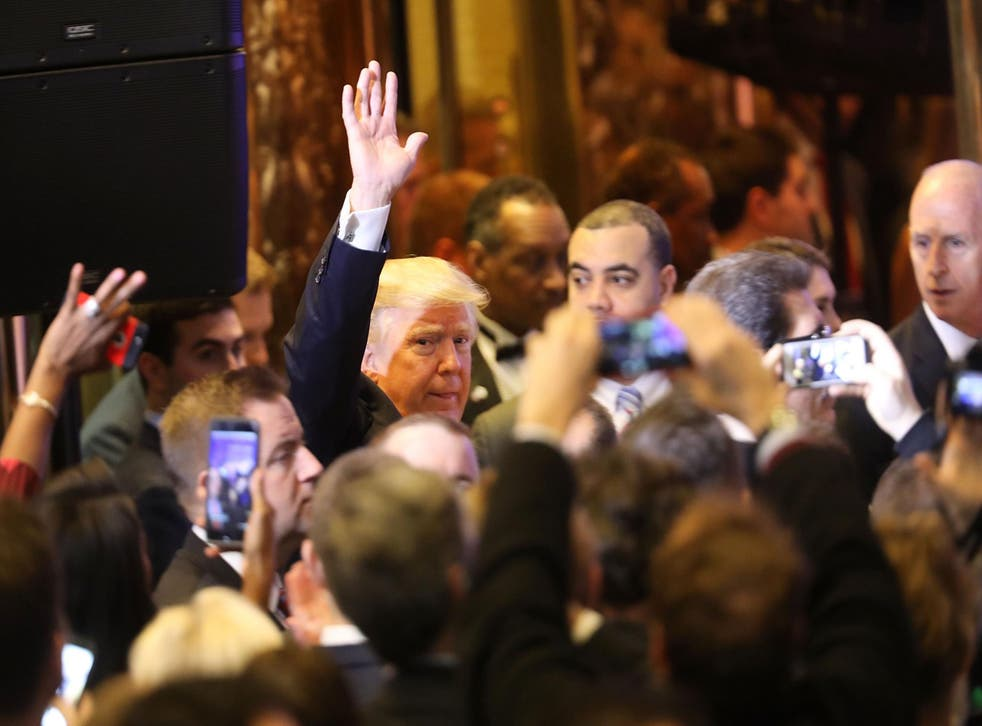 Mr Trump walks among the throng of reporters at onlookers at Trump Tower