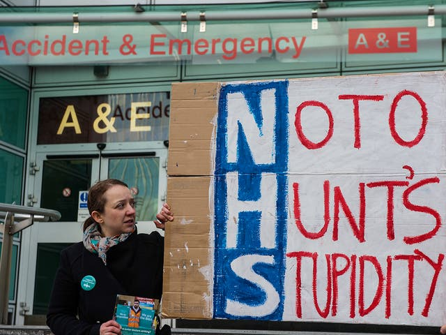 Junior doctor Dr Sioned Phillips holds a homemade placard outside the accident and emergency entrance at University College Hospital in central London