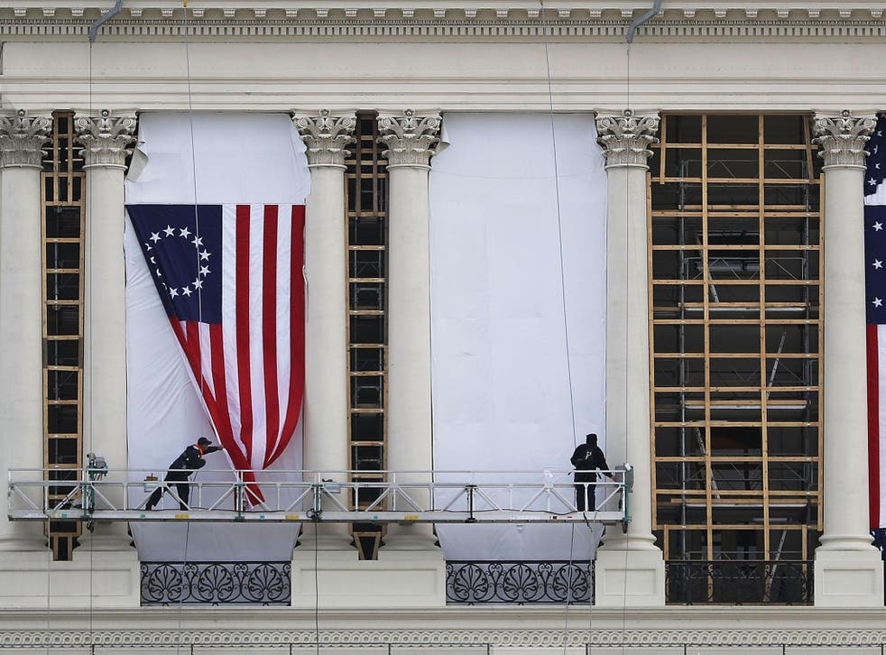 Workers hang an early version of the American flag on the U.S. Capitol to be used as part of the backdrop to the presidential inauguration for President elect Donald Trump as he prepares to take the reins of power next week