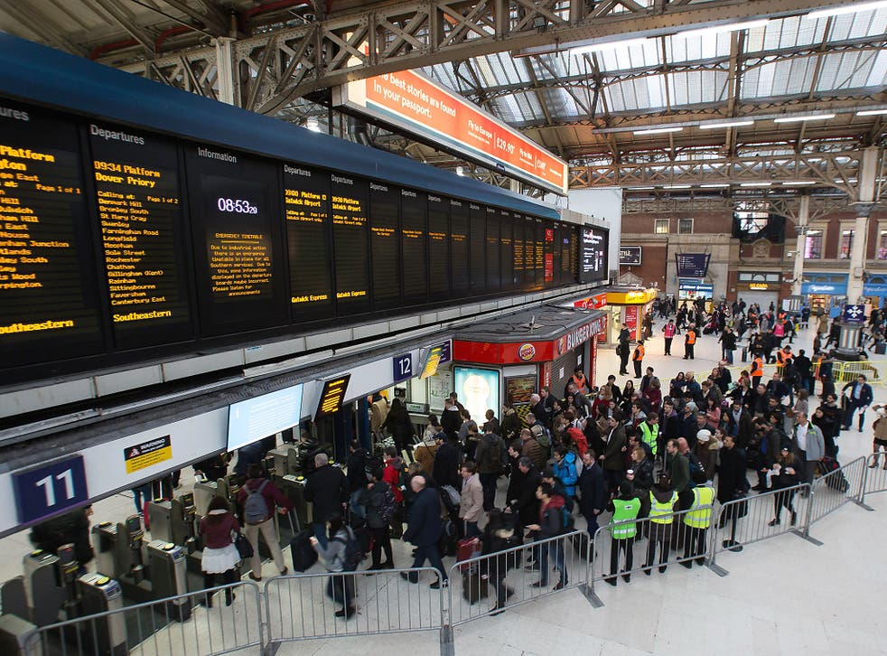 Commuters queue to take a train to Gatwick as strike action affects service at Victoria station in London