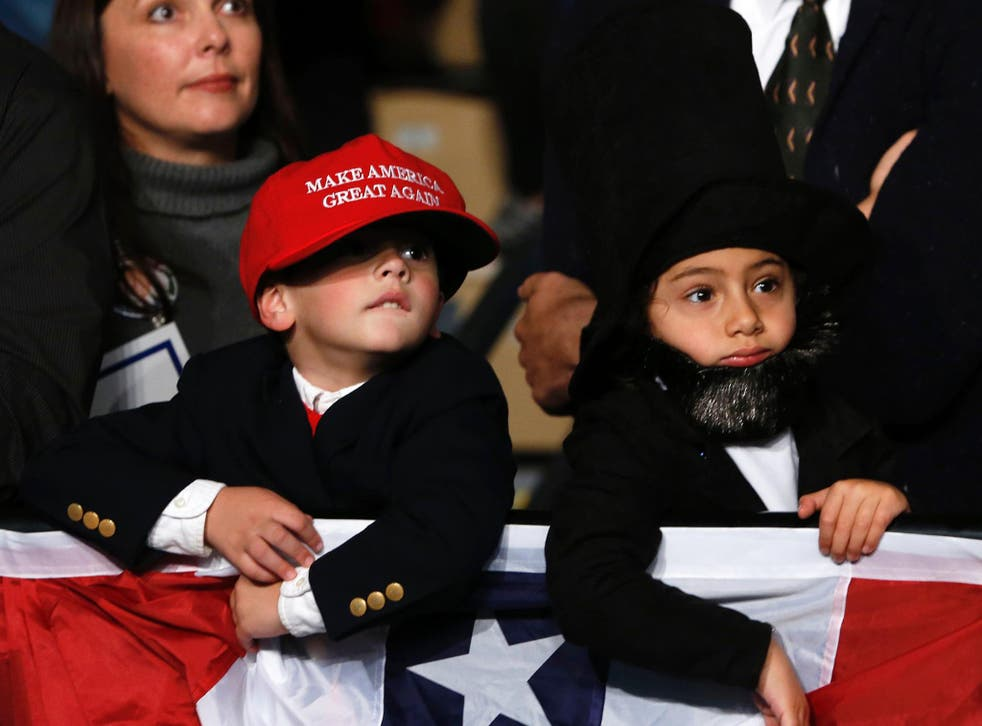 Children dressed up as Donald trump and former US President Abraham Lincoln wait to hear US Republican Presidential nominee Donald Trump address supporters at Macomb Community College