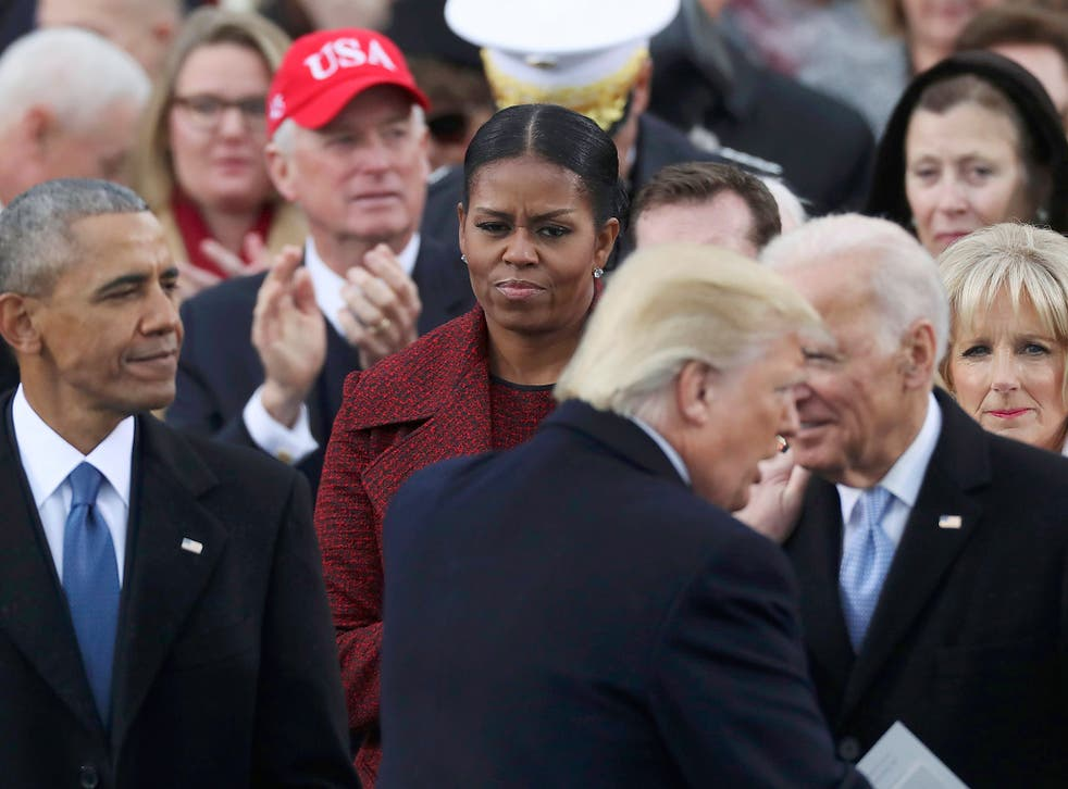 U.S. President Donald Trump shakes hands with outgoing U.S. Vice President Joe Biden as outgoing President Barack Obama and Michelle Obama look on