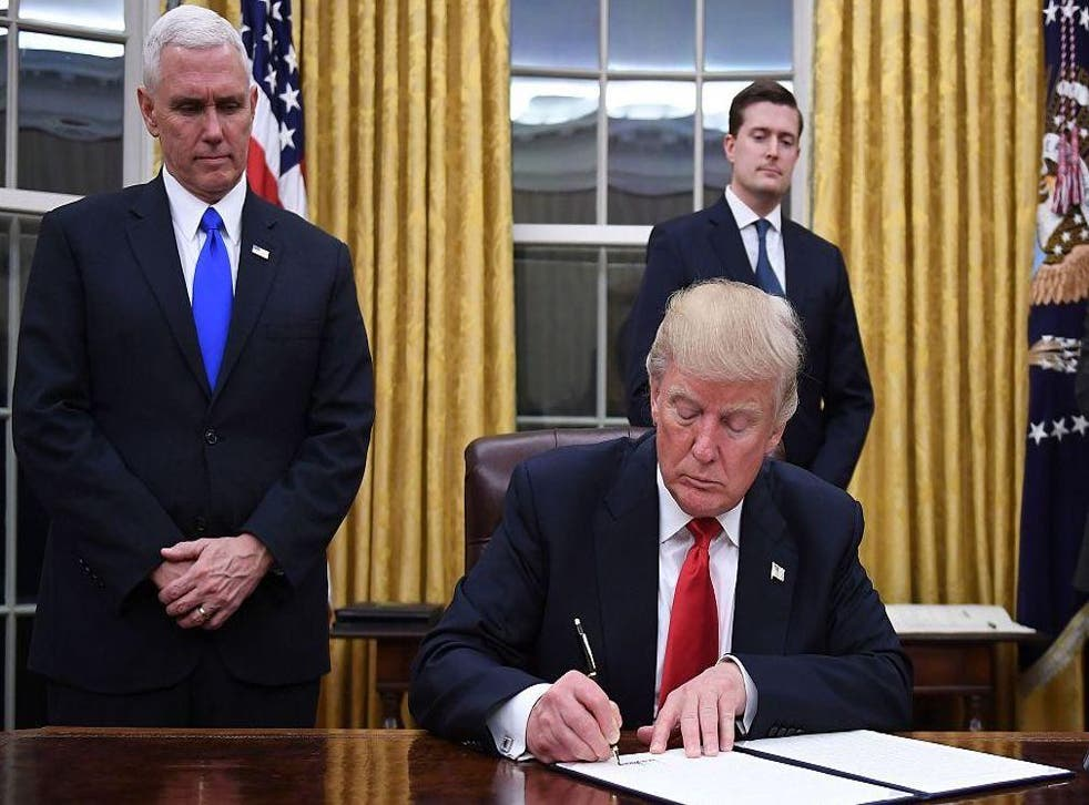 President Donald Trump signs an executive order as Vice President Mike Pence looks on at the White House in Washington, DC on January 20, 2017.