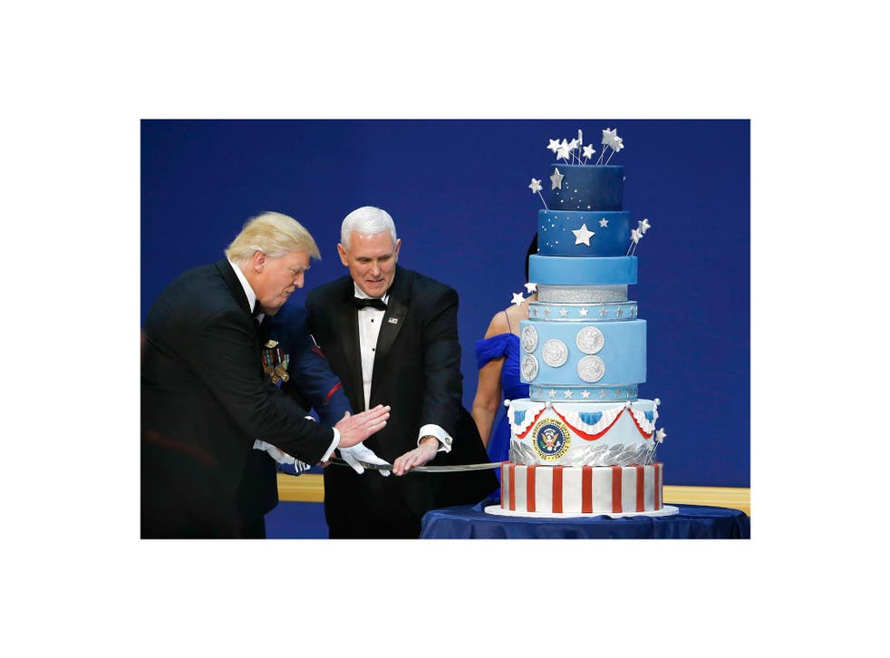 """U.S. President Donald Trump and Vice President Mike Pence prepare to cut a cake with a sword at the """"Salute to Our Armed Forces"""" inaugural ball during inauguration festivites in Washington, DC January 20, 2016. REUTERS/Rick Wilking"""
