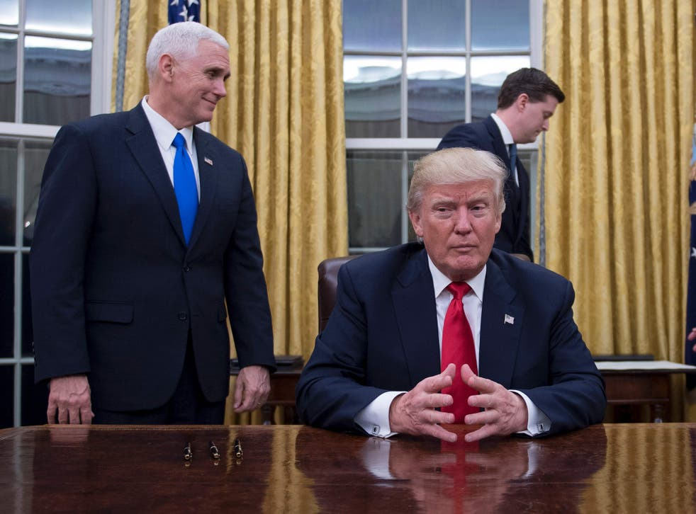 Donald Trump sits in the Oval Office for the first time, flanked by his Vice President Mike Pence and White House Chief of Staff Reince Priebus