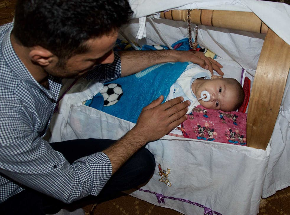Hassan Jamil, a Kurdish peshmerga fighter, with his infant son in his living room in Chrra, a town in the Kurdistan region of Iraq. The baby's name is Trump