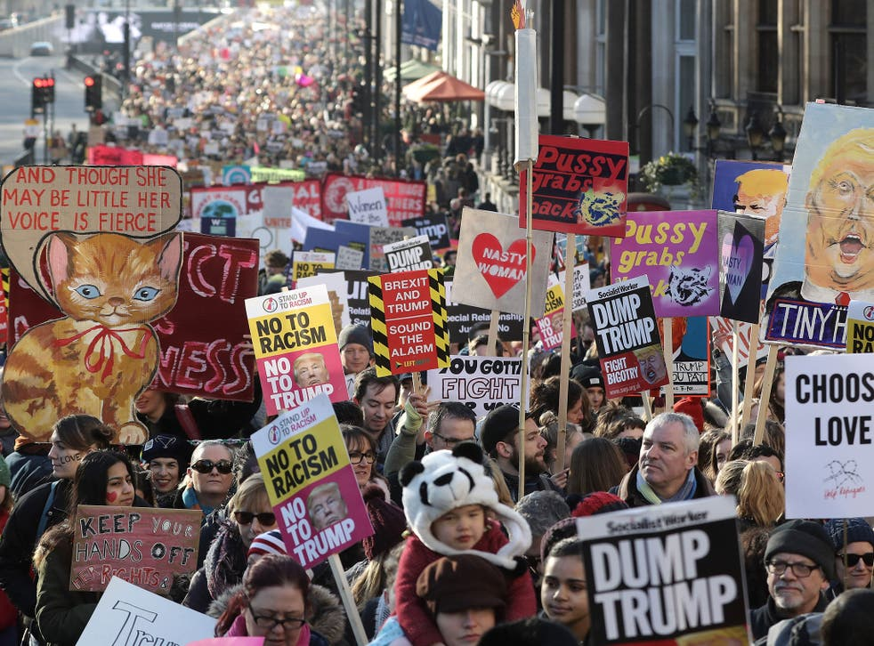 Protesters make their way through the streets of London during the Women's March on January 21, 2017 i