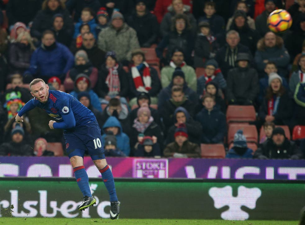 Wayne Rooney watches his free-kick head towards goal as he scores to salvage a 1-1 draw for Manchester United