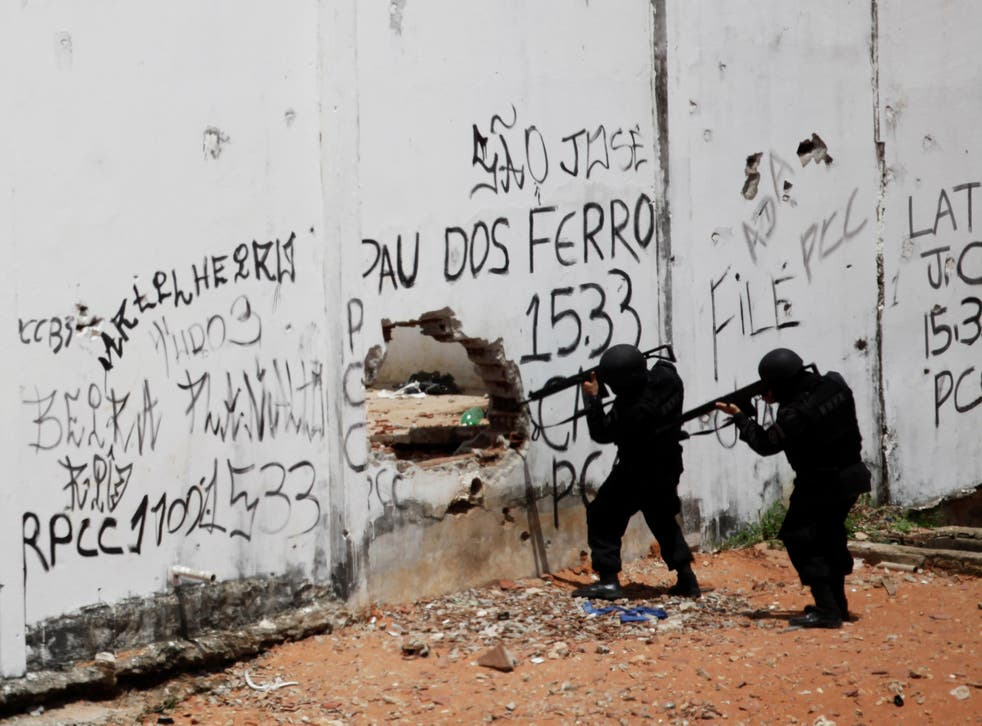 Riot policemen carry weapons during an uprising at Alcacuz prison in Natal, Brazil