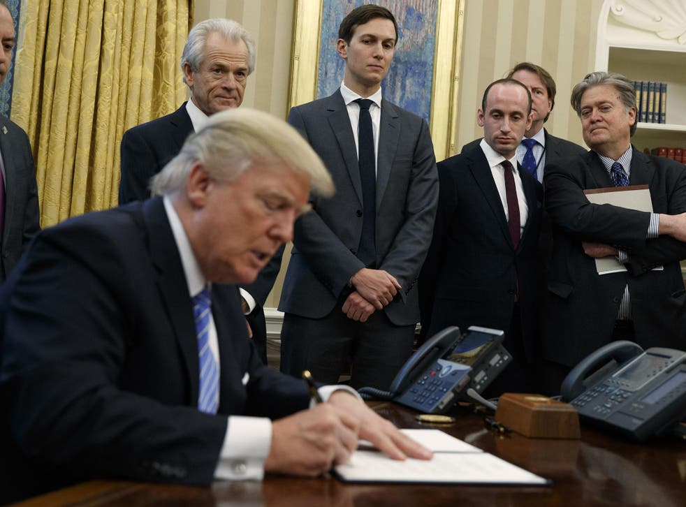Mr Trump surrounded by men as he signs an executive order