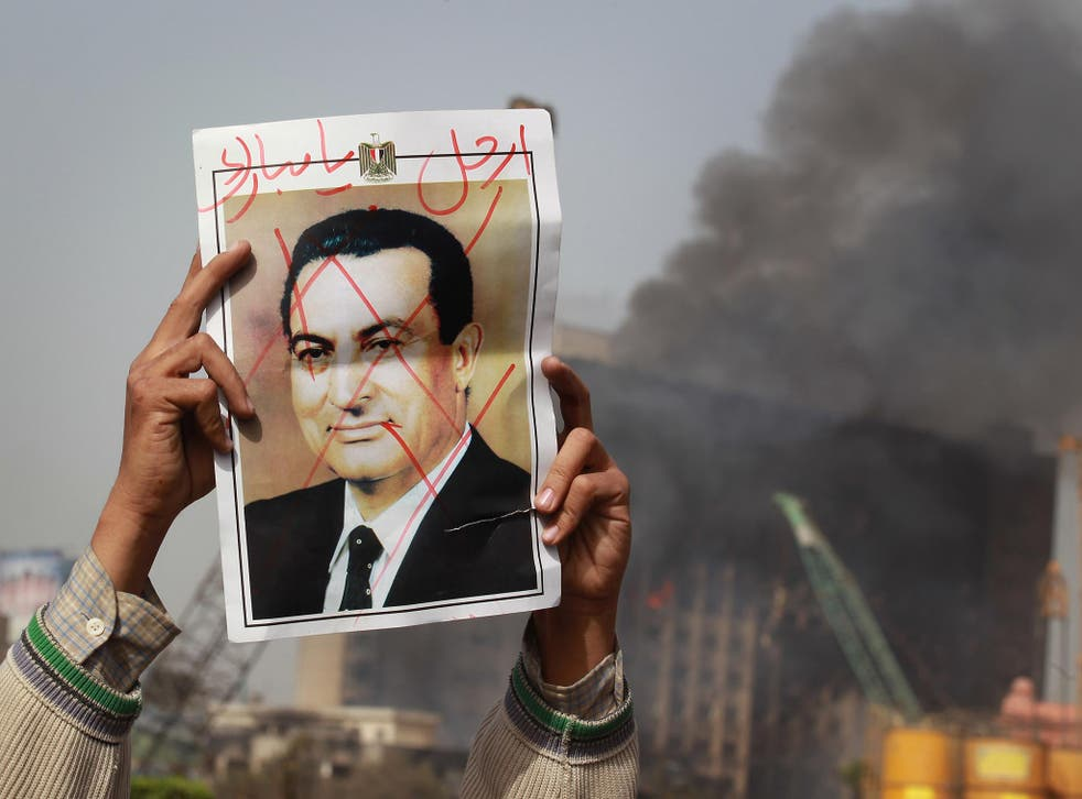 A protestor in Cairo's Tahrir Square holds a photo showing President Mubarak's face crossed out on 29 January, 2011