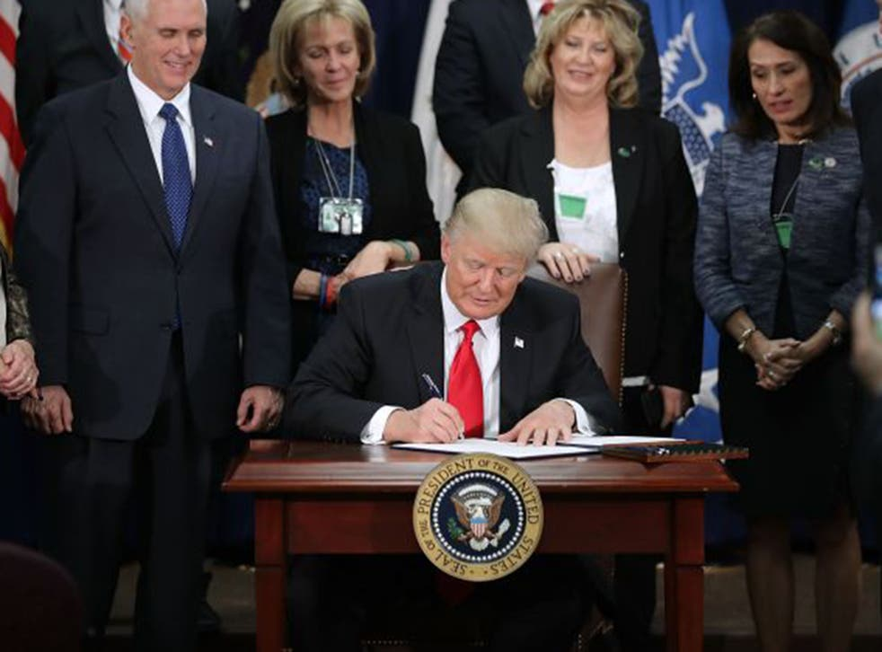 US President Donald Trump signs two executive orders during a visit to the Department of Homeland Security