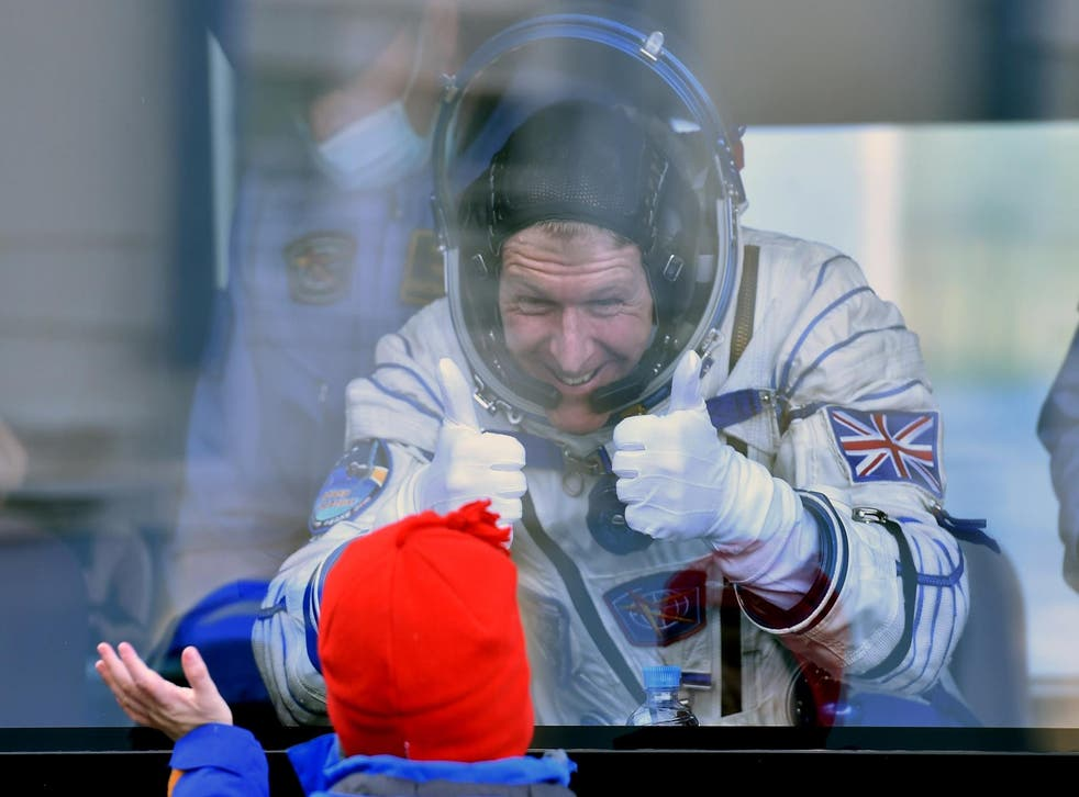 Britain's astronaut Tim Peake gestures to his child from a bus after his space suit was tested at the Russian-leased Baikonur cosmodrome, prior to blasting off to the International Space Station
