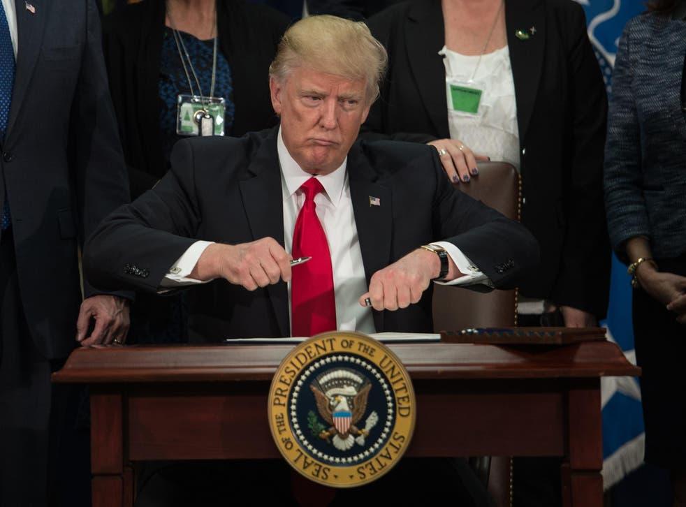 Donald Trump takes the cap off a pen to sign an executive order