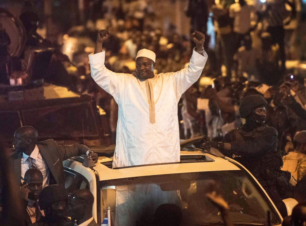People cheer as President Adama Barrow arrives nearly two months after winning an election disputed by the country's longtime dictator