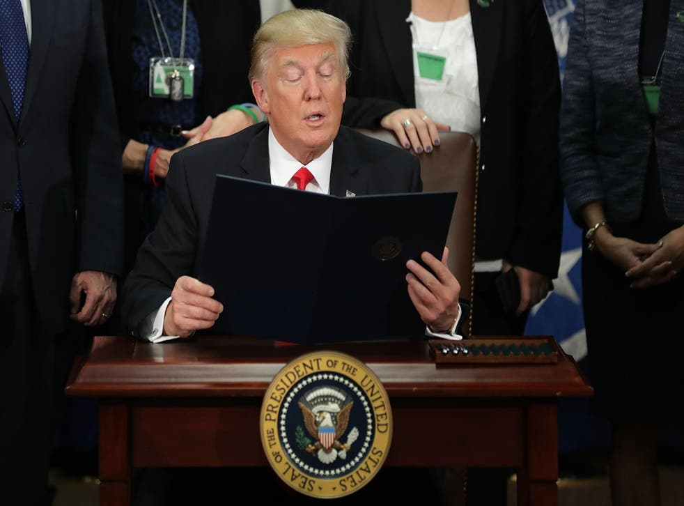 Mr Trump reading out an executive order halting the entry of refugees and people from seven majority Muslim countries
