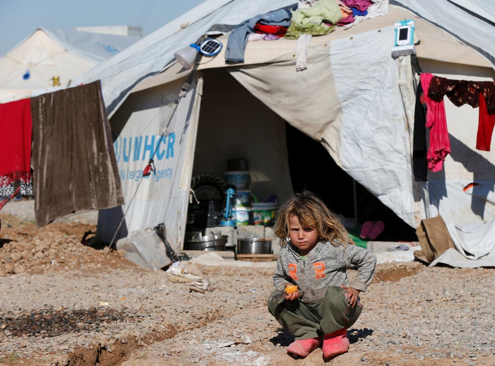 A displaced Iraqi child who fled the Isis-held city of Mosul sits in front of a tent in a camp at Hassan Sham
